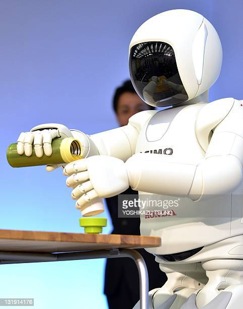 A Honda robot named 'Asimo' performs during a demonstration of its new fuctions at the company's laboratory in Wako city suburban Tokyo on November 8...