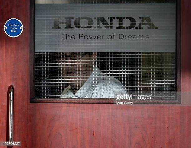 Honda worker looks out of a window in a office building at the Honda car assembly plant following the announcement that the firm is to axe 800 jobs...
