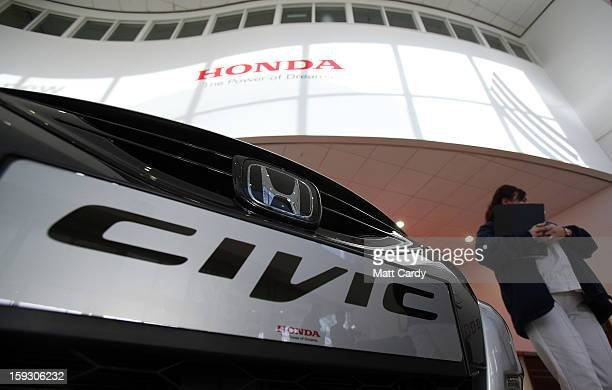 Honda worker passes a brand new Honda Civic displayed in the reception of a office building at the Honda car assembly plant following the...