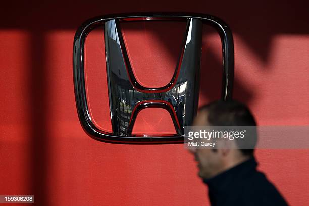 Honda worker passes a Honda logo at the Honda car assembly plant following the announcement that the firm is to axe 800 jobs on January 11 2013 in...