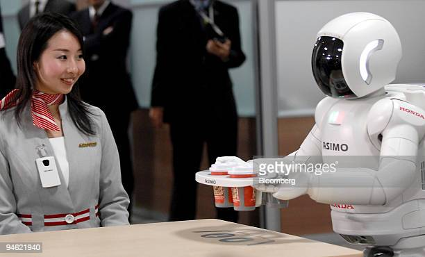 Honda's Asimo robot delivers a tray of refreshments to an office employee in Tokyo Japan on Tuesday Dec 11 2007 Honda Motor Co Japan's second largest...