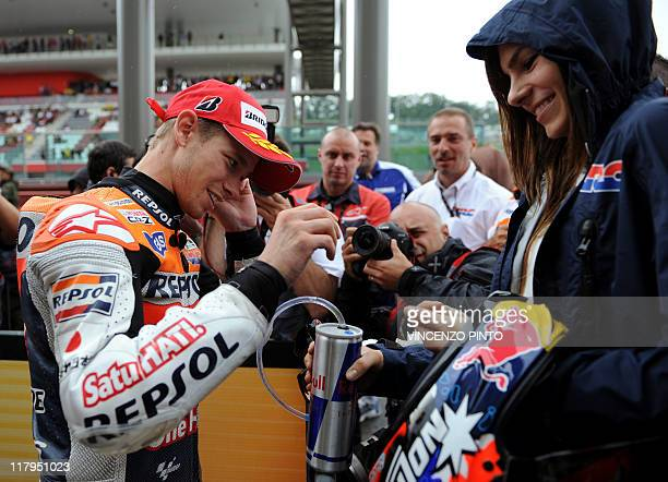 Honda's Australian Casey Stoner smiles next to his wife Adriana at the end of the MotoGP qualification practice of the Italian Grand Prix at Mugello...