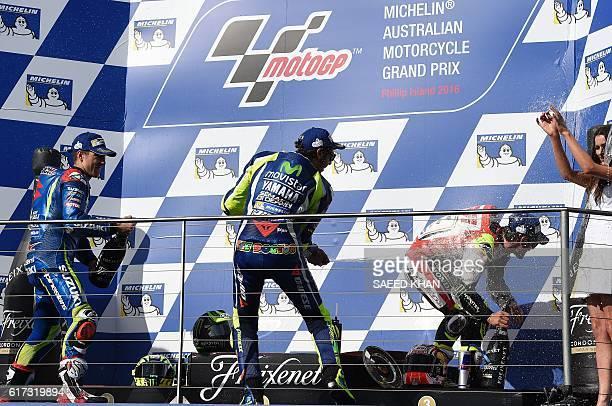 LCR Honda's British rider Cal Crutchlow celebrates his victory with secondplaced Movistar Yamaha MotoGP's Italian rider Valentino Rossi and...
