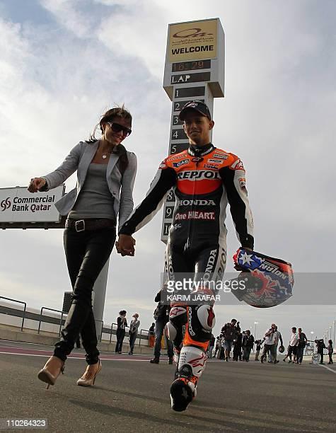 Honda's MotoGP rider Casey Stoner of Australia walks with his wife Adriana at the Losail International Circuit in the Qatari capital Doha on March...