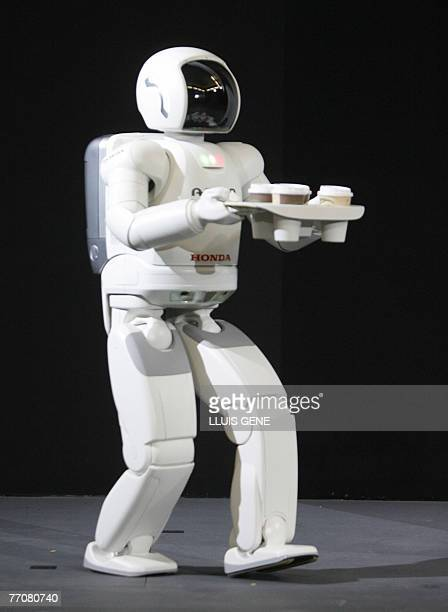 Honda's second version of the humanoid robot Asimo walks carrying a tray with drinks, 28 September 2007, in Barcelona during its first appearance in...