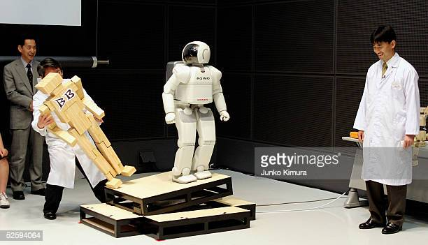 Honda's walking robot ASIMO demonstrates standing on a slope during a press conference to explain The National Museum of Emerging Science and...