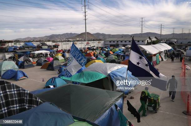 Honduran and Salvadorian flags fly over the Barretal migrant caravan camp on December 4 2018 from Tijuana Mexico After traveling more than 6 weeks...