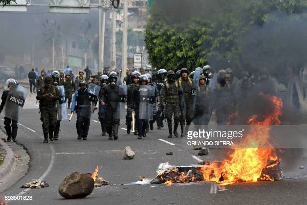 Honduran Army soldiers and police officers in riot gear clash with supporters of presidential candidate for the Opposition Alliance against...