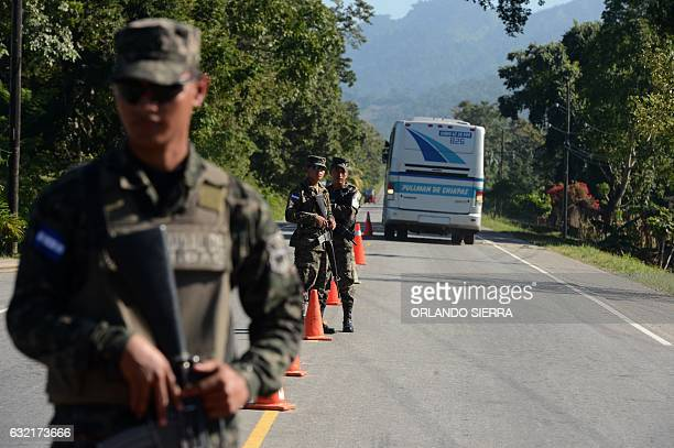 Honduran army soldiers observe a bus full of children deported from Mexico as it crosses into Honduras at Corinto on the border between Honduras and...