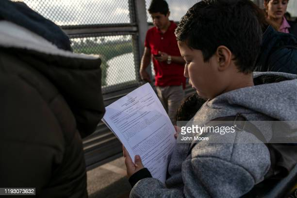 Honduran asylum seeker checks his immigration court documents while on the international bridge from Mexico to the United States on December 09 2019...