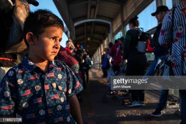 Honduran asylum seeker Christopher stands with his father on the international bridge from Mexico to the United States on December 09 2019 in the...