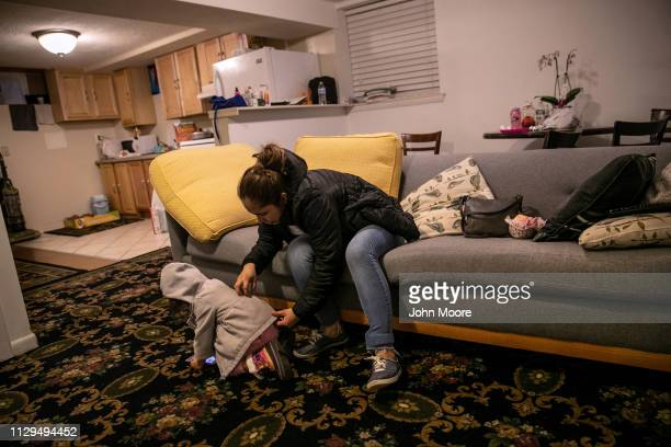 Honduran asylum seeker Sandra Sanchez adjusts the coat of her daughter Yanela Sanchez 2 1/2 in the basement apartment they share with fellow...