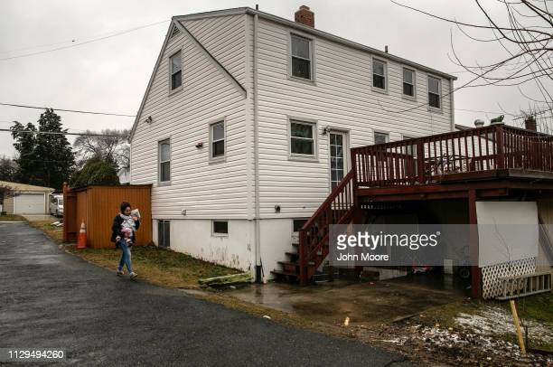 Honduran asylum seeker Sandra Sanchez carries her daughter Yanela Sanchez 2 1/2 to their basement apartment on February 11 2019 in the greater...