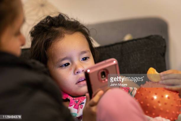 Honduran asylum seeker Yanela Sanchez 2 1/2 watches videos on her mother's phone in the basement apartment they share with other immigrants on...