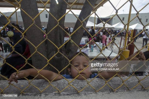 Honduran boy looks through a fence from inside a warehouse used as a shelter for migrants in Piedras Negras Coahuila state Mexico on the US border on...
