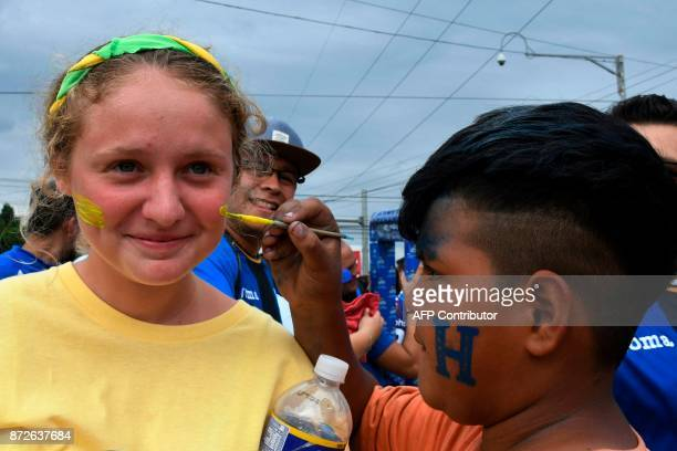 A Honduran boy paints the face of an Australian fan before the start of the first leg football match of the 2018 World Cup qualifying playoff against...
