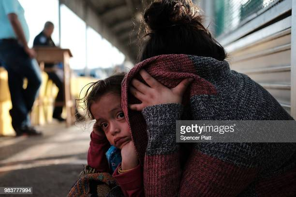 Honduran child and her mother, fleeing poverty and violence in their home country, waits along the border bridge after being denied entry from Mexico...