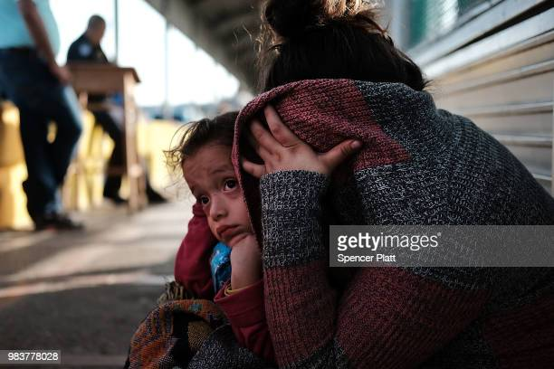 Honduran child and her mother fleeing poverty and violence in their home country waits along the border bridge after being denied entry from Mexico...