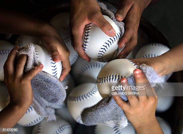 Honduran children clean softballs 05 march 2002 made at a factory in Macuelizo Santa Barbara Honduras 320 kms northwest of Tegucigalpa Workers...
