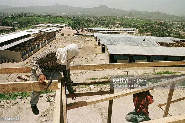 Honduran construction workers continue to build homes 06 July 1999 near Tegucigalpa for people left homeless by Hurricane Mitch Victims of the...