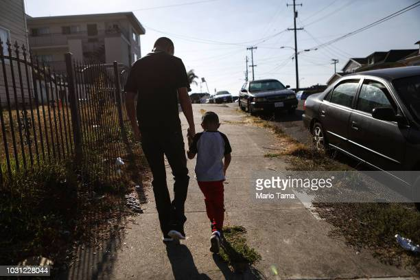 Honduran father Juan and his sixyearold son Anthony walk on their way to attend Sunday Mass on September 9 2018 in Oakland California They fled their...