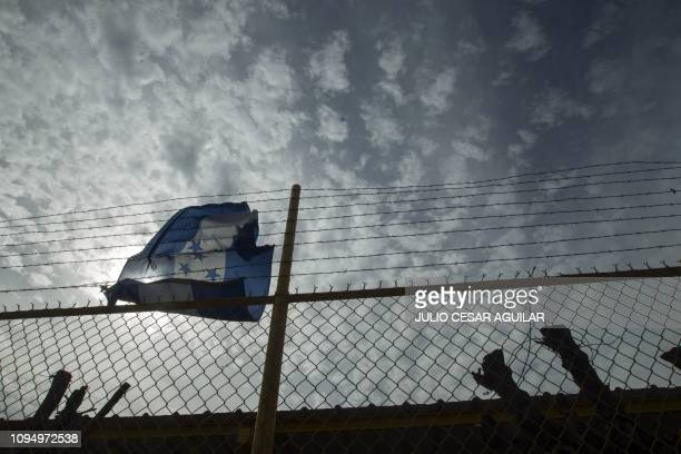 A Honduran flag is seen outside a warehouse used as a hostel for Central American migrants in Piedras Negras Coahuila state Mexico on February 7 2019...
