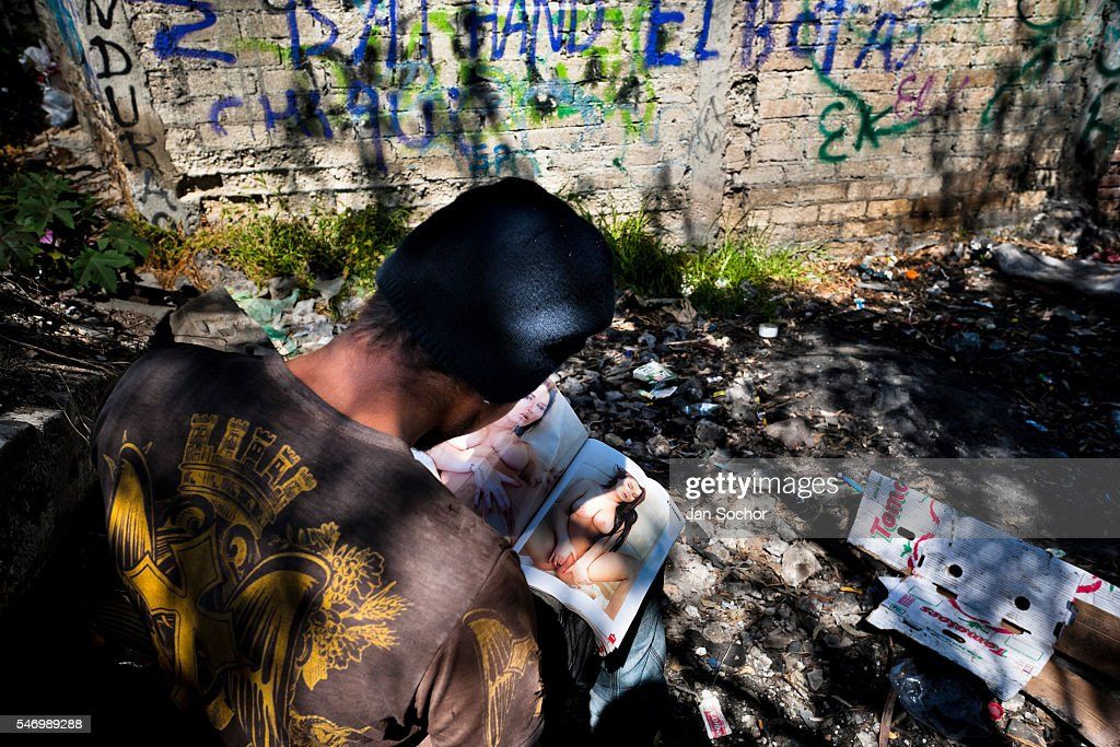 A Honduran immigrant browses through a US porn magazine while waiting near the railroad track to climb up the cargo train known as La Bestia (The Beast) in Lechería station, in the outskirts of Mexico City, Mexico, 6 November, 2014. Between 2010 and 2015, the US and Mexico have apprehended almost 1 million illegal immigrants from El Salvador, Honduras, and Guatemala. While the economic reasons remain the most frequent motivation for people from Central America to illegally immigrate to the US, thousands of Salvadorans, Guatemalans, and Hondurans, many of them minors, seek asylum in the US due to the thriving crime and gang-related violence in their region (known as the Northern Triangle). Taking an exhausting and risky journey, riding thousands of miles atop the cargo trains, facing a physical danger and extortion from the organized crime groups that control migrant routes, the undocumented still flee to the US, looking for their American dream.