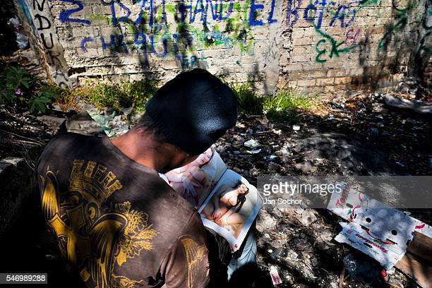 Honduran immigrant browses through a US porn magazine while waiting near the railroad track to climb up the cargo train known as La Bestia in...