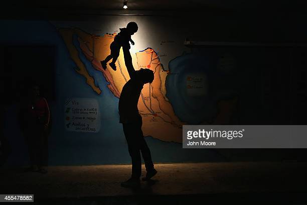 Honduran immigrant entertains a fellow immigrant's child in front a map of Mexico showing train routes leading north at a shelter for undocumented...