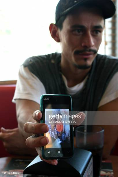 Honduran immigrant Ever Sierra who was deported from the US shows a picture of his family after arriving in San Pedro Sula Honduras on June 22 2018...