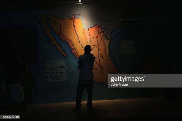 Honduran immigrant inspects map of Mexico showing train routes leading north at a shelter for undocumented immigrants on September 14 2014 in...