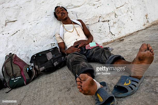 Honduran immigrant wounded by a fall of the train waits to catch the cargo train called La Bestia on a train station in a border town of Arriaga...