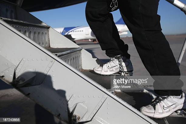 Honduran immigration detainee, his feet shackled and shoes laceless as a security precaution, boards a deportation flight to San Pedro Sula, Honduras...