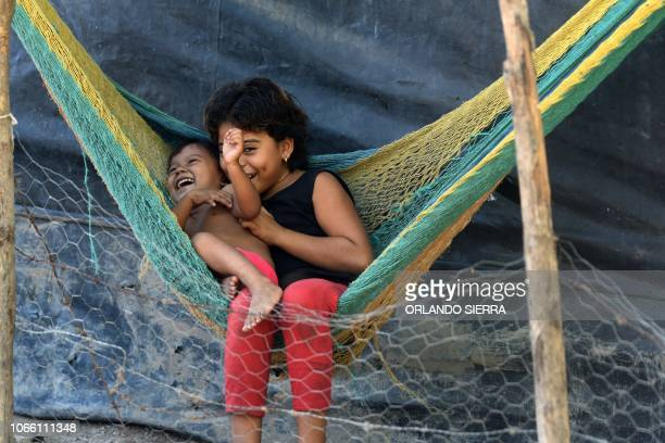 TOPSHOT Honduran Loani Nicole plays with her sister Madelin Melissa at their grandfather's house after their mother Luz Marina Cruz left in a caravan...