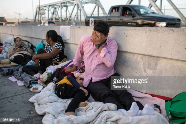 Honduran man and his 5yearold son wait on the Mexican side of the Brownsville Matamoros International Bridge after being denied entry into the US on...