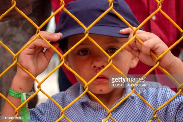 A Honduran migrant boy looks thorugh the fence of a warehouse used as shelter in Piedras Negras Coahuila Mexico in teh border with the US on February...