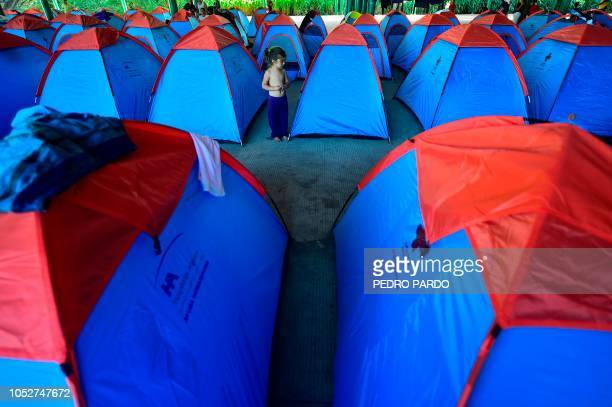 A Honduran migrant child heading in a caravan to the US is seen next to tents at the International Mesoamerican Fair's venue in Tapachula Chiapas...