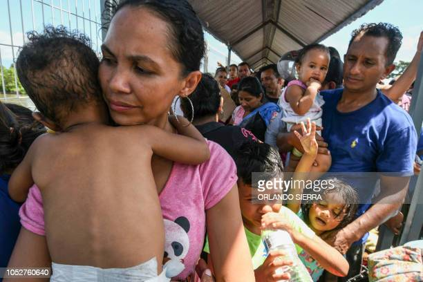 A Honduran migrant couple and their five kids taking part in a caravan heading to the US wait to cross the border from Ciudad Tecun Uman in Guatemala...