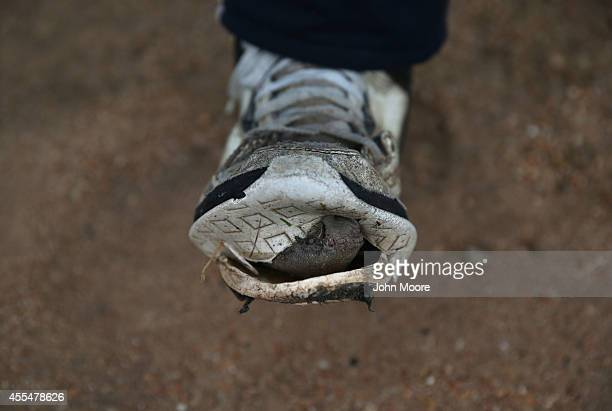 Honduran migrant displays a weathered shoe after walking to a shelter for undocumented immigrants on September 14 2014 in Tenosique Mexico The...