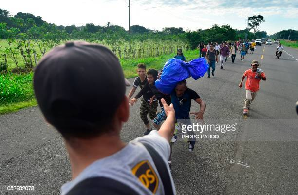 A Honduran migrant extends his hand to a fellow man from a truck as they take part in a caravan heading to the US on the road linking Ciudad Hidalgo...