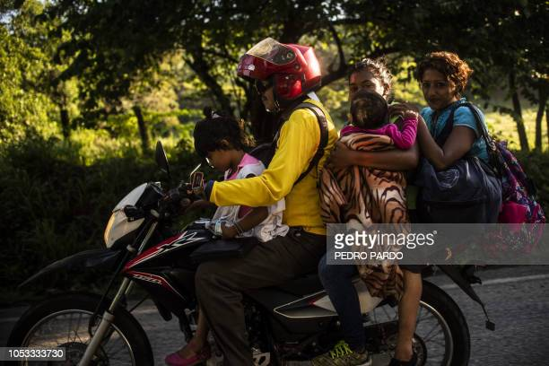Honduran migrant family heading in a caravan to the US travels on a motorbike near Mapastepec southern Mexico on October 25 2018 Thousands of Central...