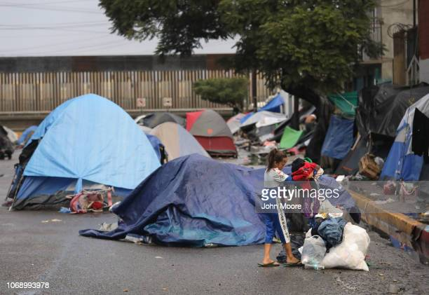 Honduran migrant Fielina dumps used wet clothing into a trash pile outside a closed temporary migrant shelter near the USMexico border fence on...