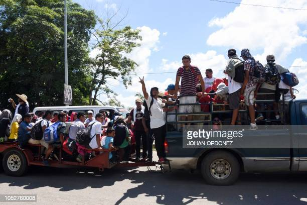 A Honduran migrant flashes the V sign as he travels alongside fellow men onboard trucks as they head in a caravan to the US in the outskirts of...