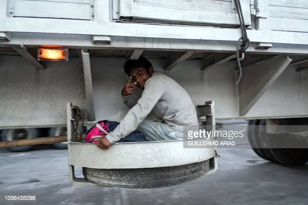 A Honduran migrant heading in a caravan to the US flashes the V sign from a truck on the road linking Matias Romero and Donaji Oaxaca State Mexico on...