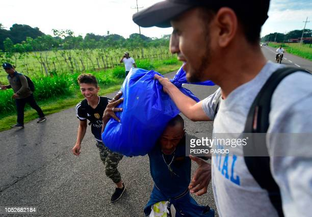 A Honduran migrant helps a fellow man from a truck as they take part in a caravan heading to the US on the road linking Ciudad Hidalgo and Tapachula...