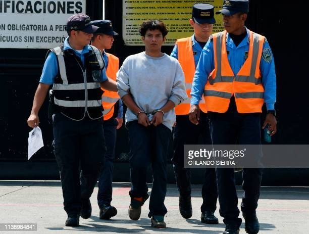 A Honduran migrant is escorted as he arrives at the Ramon Villeda Morales airport in San Pedro Sula 180 km north of Tegucigalpa on April 11 after...