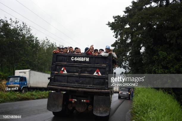 TOPSHOT Honduran migrants aboard a truck head in a caravan to the United States in the outskirts of Mazatenango Suchitepequez departament 160 km...