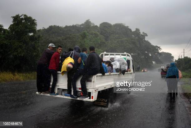 Honduran migrants aboard a truck head to the United States in a caravan under heavy rain in Siquinala municipality Escuintla departament 60 km south...