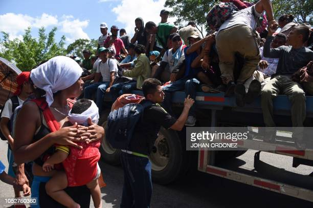 Honduran migrants board a truck as they take part in a caravan heading to the US in the outskirts of Tapachula on their way to Huixtla Chiapas state...