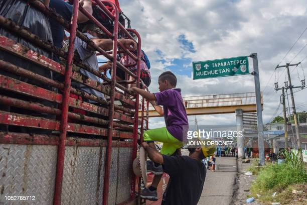 TOPSHOT Honduran migrants board a truck as they take part in a caravan heading to the US in the outskirts of Tapachula on their way to Huixtla...